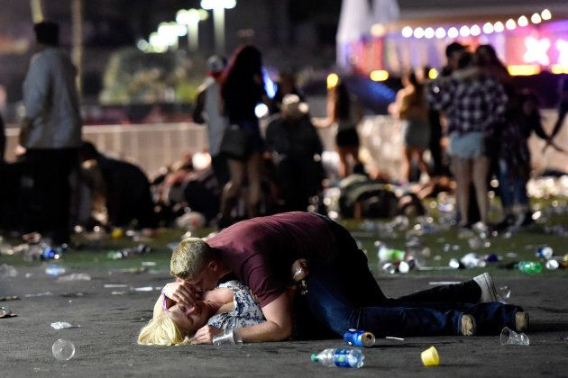 A man lays on top of a woman as others flee the Route 91 Harvest country music festival grounds after...
