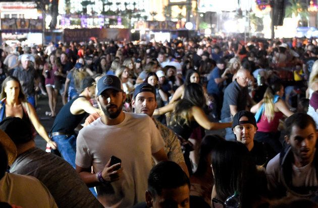 People flee the Route 91 Harvest country music festival grounds after a shooter was reported on Sunday...