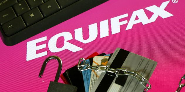 Credit cards, a chain and an open padlock is seen in front of displayed Equifax logo in this illustration...