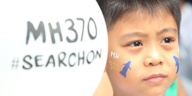 A Malaysian child holds a balloons and gets his face painted for the victims of the missing MH370 airplane...