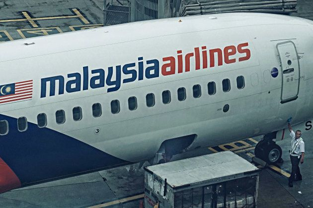 Malaysian Airlines ramp crews unloading the cargo from an aircraft at the busy terminal of Kuala Lumpur...