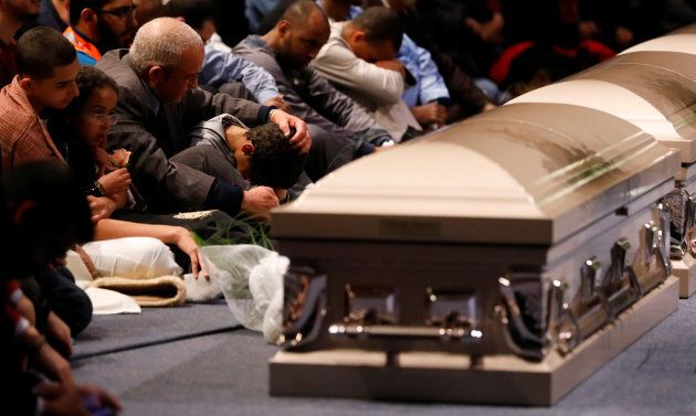 A young mourner is comforted during a funeral ceremony on Feb. 3, 2017 for three of the victims of the...