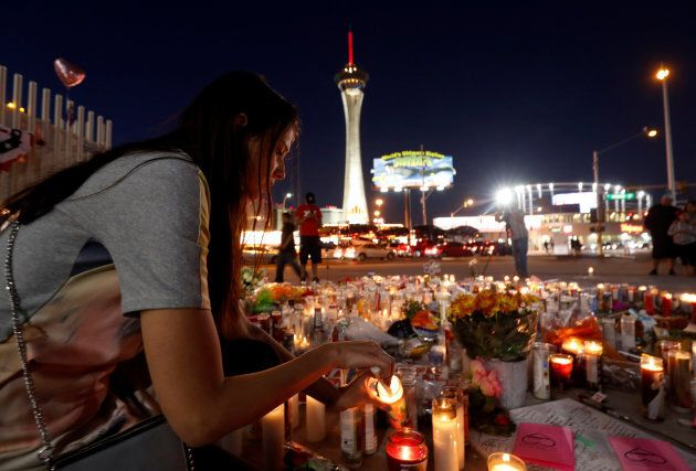 Dashenka Giraldo of Las Vegas lights candles at a makeshift memorial for shooting victims at the Las...