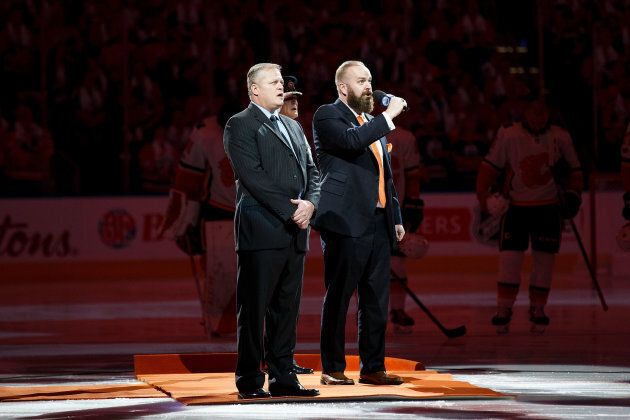 Edmonton Police Service Const. Michael Chernyk, left, sings the Canadian anthem with Edmonton Oilers...