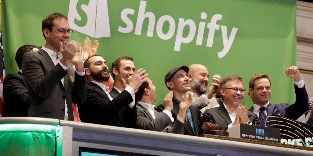Shopify CEO Tobias Lutke (centre wearing hat) rings the New York Stock Exchange opening bell, marking...