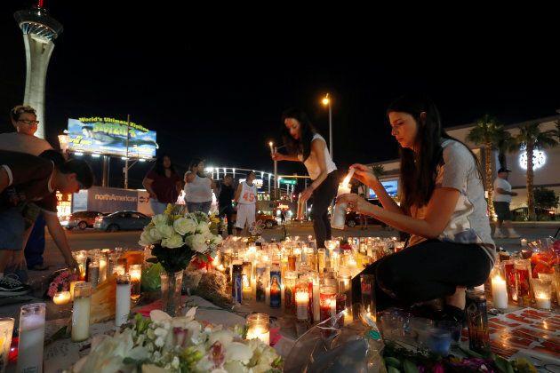 Elisabeth Apcar and her cousin Dashenka Giraldo, both of Las Vegas, light candles at a makeshift memorial...