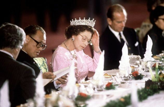 The Queen reading the menu before dinner is served at a banquet, (Photo by Tim Graham/Getty