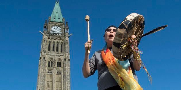 Chief Marcia Brown Martel sings outside the Parliament buildings following a news conference announcing...