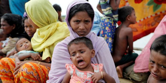 Rohingya refugees wait in a rice field after crossing the border in Palang Khali, Bangladesh, Oct. 9,