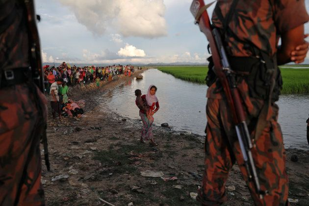 Bangladeshi border guards watch as Rohingya refugees who fled from Myanmar make their way through the...