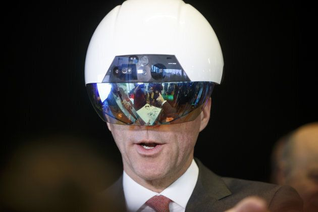 Bill Morneau, Canada's finance minister, tries on a virtual reality helmet during an artificial intelligence...
