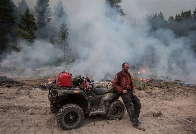 B.C. Wildfire Service firefighter Jordain Lamothe takes a brief break while conducting a controlled burn to help prevent the Finlay Creek wildfire from spreading near Peachland, B.C., on Sept. 7, 2017.