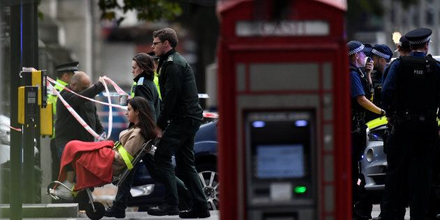 Emergency first responders wheel a woman in a wheelchair to an ambulance near the Natural History Museum,...
