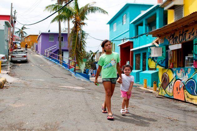 Two girls walk on a street in the neighbourhood of La Perla in the aftermath of Hurricane Maria in San...