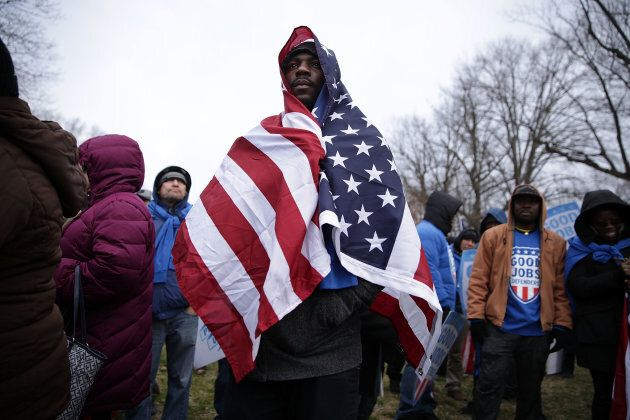 Fast food chain worker Tino Akata of Silver Spring, Maryland, wraps a U.S. flag around himself during...