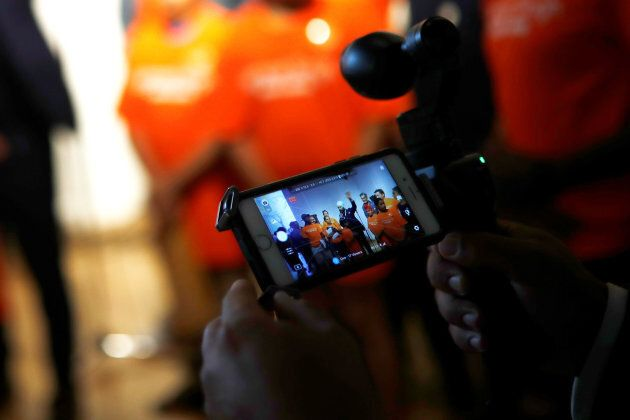 A man live streams New Democratic Party federal leadership candidate Jagmeet Singh as he speaks at a meet and greet event in Hamilton, Ont. on July 17, 2017.