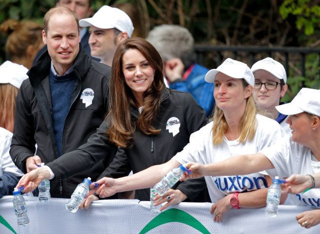 Prince William, Duke of Cambridge & Catherine, Duchess of Cambridge hand out water to runners taking...