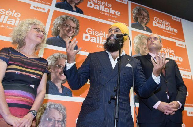 NDP Leader Jagmeet Singh responds to reporters questions during a campaign visit for local candidate Gisele Dallaire, left, as MP Guy Caron watches on Oct. 10, 2017 in Alma, Quebec.