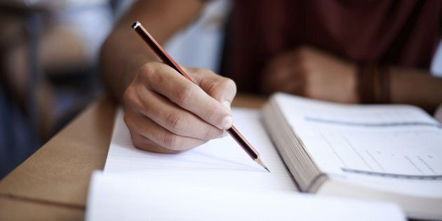 Closeup shot of a young man writing on a note