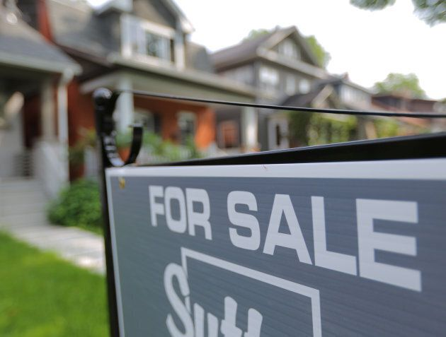 A sign advertises a house for sale as Canada's central bank announced its first interest rate hike in...