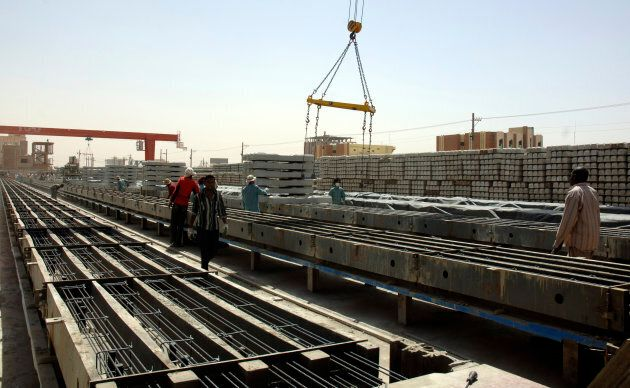 Chinese and Sudanese labourers work on the production of railway tracks at the Shanghai Huibo factory...