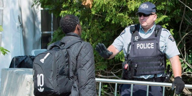 An asylum seeker, claiming to be from Eritrea, is questioned by an RCMP officer as he crosses the border...
