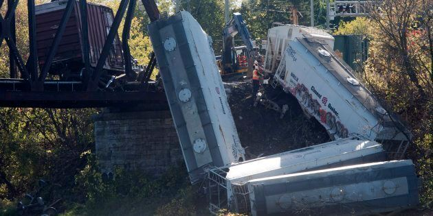 Workers clear up debris after a train derailment on Oct. 13, 2017 on Laval, Que., east of Montreal. No...