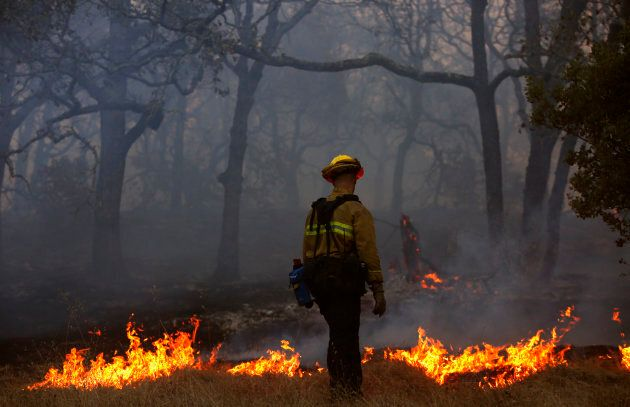 A firefighter with the Marin County Fire Department works a backfire in the Oakmont community along Highway...