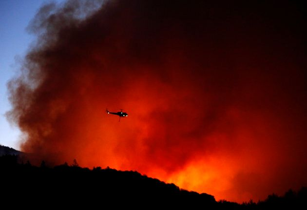 A helicopter prepares to drop water on a fire that threatens the Oakmont community along Highway 12 in...