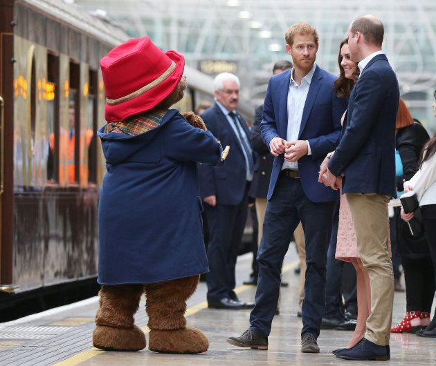 Britain's Catherine the Duchess of Cambridge, Prince William and Prince Harry stand next to a costumed figure of Paddington bear on platform 1 at Paddington Station, as they attend the Charities Forum in London, October 16, 2017.