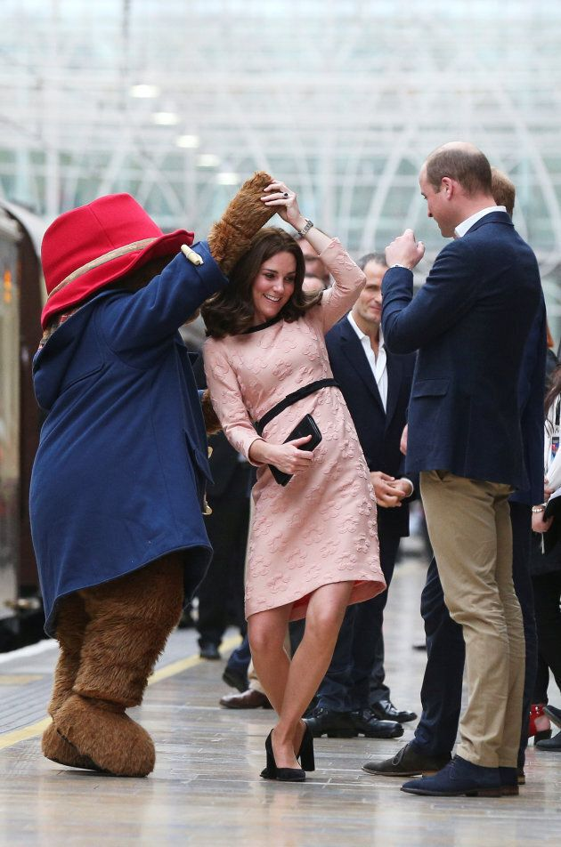 Britain's Prince William watches as his wife Catherine the Duchess of Cambridge dances with a costumed...