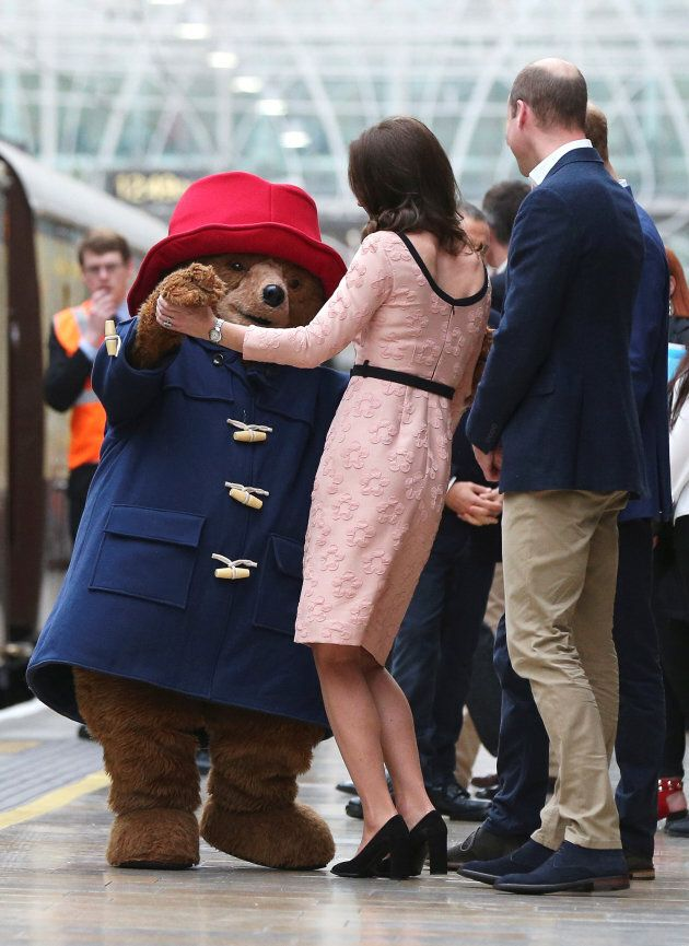 Britain's Prince William watches as his wife Catherine the Duchess of Cambridge dances with a costumed figure of Paddington bear on platform 1 at Paddington Station, as they attend the Charities Forum in London, October 16, 2017.