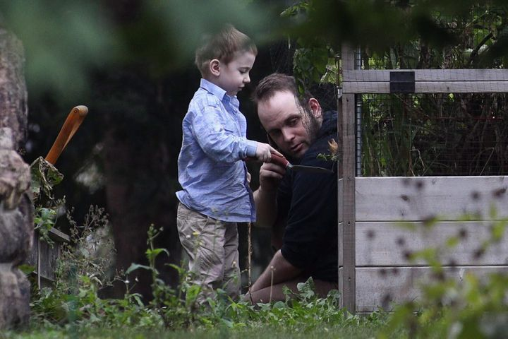Joshua Boyle and one of his kids play in the garden at his parents' house in Smiths Falls, Ont., on Saturday, Oct. 14, 2017.