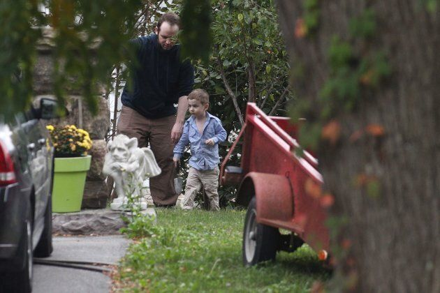 Joshua Boyle and one of his kids play in the garden at his parents house in Smiths Falls, Ont. on