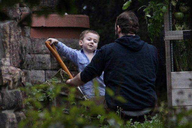 Joshua Boyle and one of his kids play in the garden at his parents house in Smiths Falls, Ont., on Saturday,...