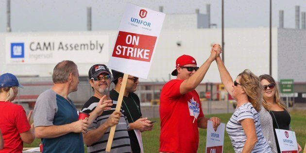 Employees of the GM CAMI assembly factory stand on the picket line in Ingersoll, Ont., on Sept. 18,