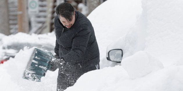 Danny Luis shovels snow around his car after a late winter storm in Montreal on March 15,