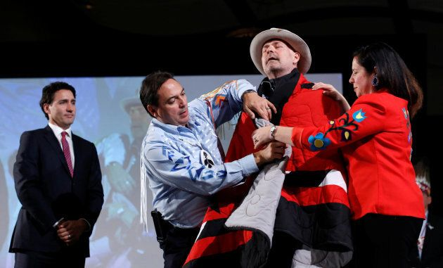 Prime Minister Justin Trudeau looks on as Gord Downie is presented with a blanket during an honouring ceremony at the Assembly of First Nations Special Chiefs Assembly in Gatineau, Quebec, Canada, Dec. 6, 2016. (REUTERS/Chris Wattie)
