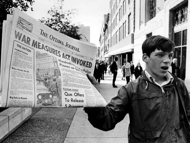 A newsboy holds up a newspaper with a banner headline reporting the invoking of the War Measures Act,...