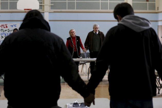 Canada's Indigenous Affairs Minister Carolyn Bennett, centre left, and New Democratic Party MP Charlie Angus, centre right, take part in a prayer at the start of a meeting with youth in the Attawapiskat First Nation in northern Ontario, April 18, 2016 after a suicide crisis state of emergency was declared.