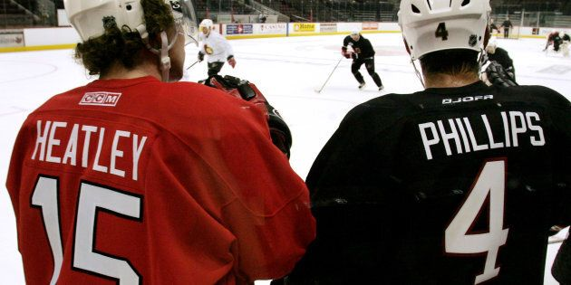 Then-Ottawa Senators Dany Heatley (L) and Chris Phillips watch their teammates during the second day...