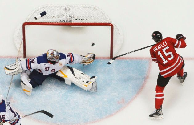 Dany Heatley of Canada scores a goal past goalie Ryan Miller of the U.S. in second period of their hockey...