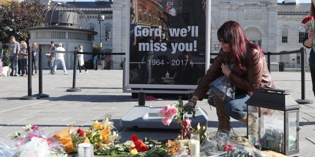 A woman places flowers at a growing memorial for the late Gord Downie, lead singer of the Tragically...