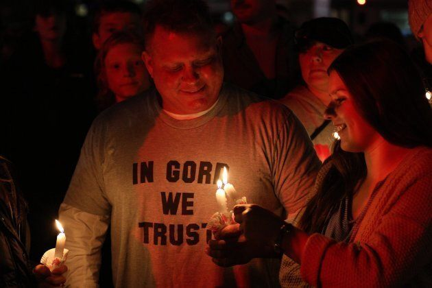 People stand with candles during a vigil for Gord Downie of the Tragically Hip in downtown Kingston,...