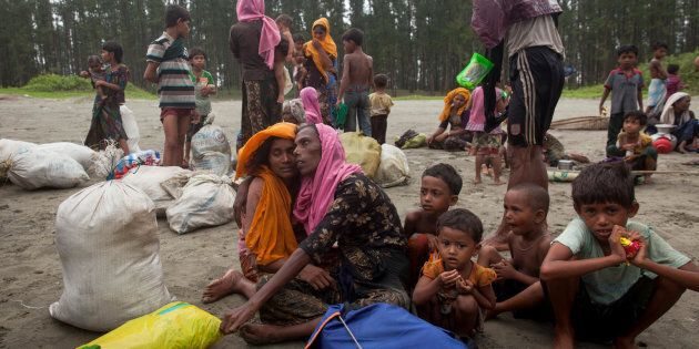 On Sept. 7, 2017, newly arrived Rohingya refugees sit at Shamlapur beach in Cox's Bazar district in Bangladesh,...