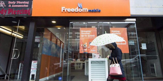 A woman walks past the rebranded signage of Freedom Mobile, in Toronto on Nov. 24, 2016. Freedom Mobile's...