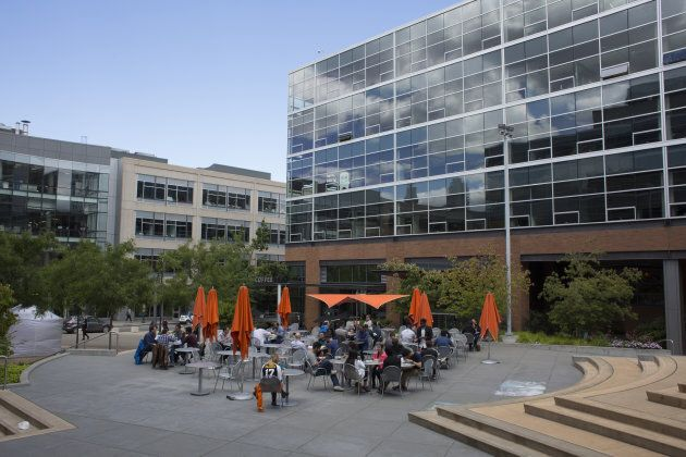 People eat lunch in a courtyard outside of the Amazon.com Inc. headquarters in the South Lake Union neighborhood...
