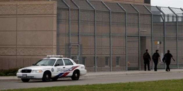 Officers walk by a police car in front of the Toronto South Detention Centre on May 24,