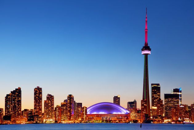 The CN Tower and the Rogers Centre aglow in the Toronto skyline during
