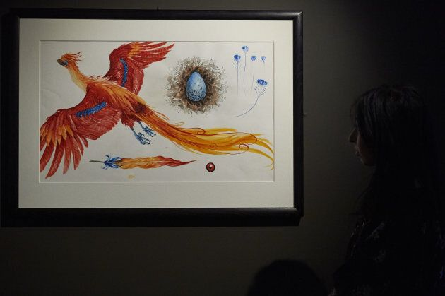 An exhibition curator stands next to an illustration of Fawkes the Phoenix during a preview of 'Harry...